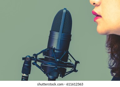 asian female singer mouth singing on microphone, isolated on green. art filter