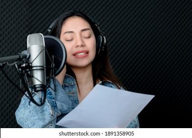 Asian female singer singing in a recording studio. Female singer singing and playing guitar.