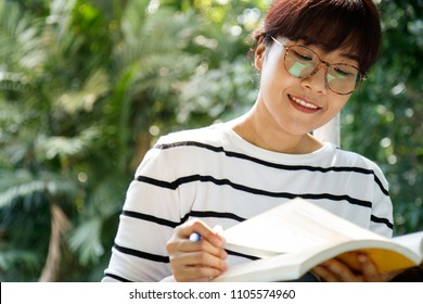 Asian female student doing the homework with diligence while sitting in the university. Selective focus. Copy space.