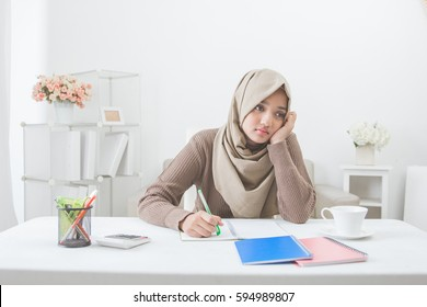 asian female student with hijab tired of doing homework