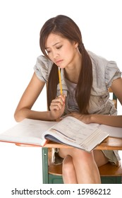 Asian female student is sitting by the desk. She is studying huge math book, preparing to test