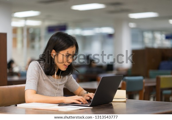 asian female student study and working with laptop computer in university library