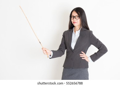 Asian female teacher hand holding a cane in class lesson, standing on plain background.