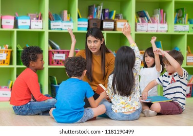 Asian female teacher teaching and asking mixed race kids hand up to answer in classroom,Kindergarten pre school concept