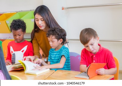 Asian female teacher teaching diversity kids reading book in classroom,Kindergarten pre school concept