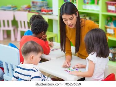 Asian female teacher teaching mixed race kids reading book in classroom,Kindergarten preschool concept.