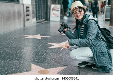 asian female tourist finger pointed star plaques of honored celebrities on Hollywood Boulevard in Los Angeles on sunny day. woman backpacker kneeling down on walk ground showing camera smiling