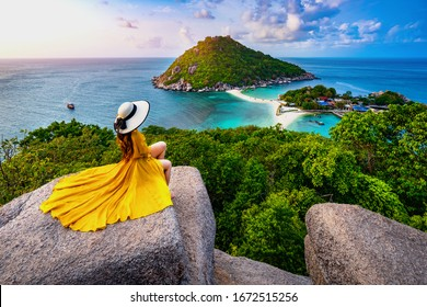 Asian female tourist poses for a photo shoot at the viewpoint on Nang Yuan island, Thailand
