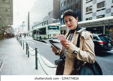asian female tourist using online city guide on smartphone gps in urban street searching locations. young girl traveler self guided travel trip in kyoto japan standing on busy street holding map.