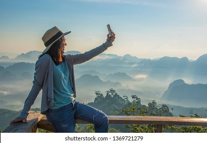 Asian female tourists resting or relaxing vacation  on a long holiday to travel, selfie herself with a mobile phone, Doi Tapang viewpoint, Chumphon, Thailand