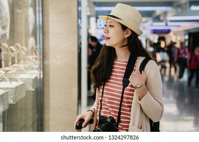 asian female travel photographer standing outside showing window of watch jewelry shop in duty free zone. chinese young girl tourist in hat window shopping in tax free area finding buying present.