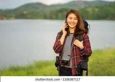 Asian female traveling lost in the woods forest. women try to get signal on her phone,she finds direction talking to a friend and have fun,beautiful young girl using smartphone outdoor,travel concept