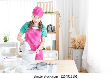 asian female use electric dough mixer in kitchen room, bakery learning activity, she cooking homemade bakery and feeling happy