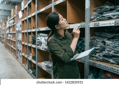 asian female warehouse worker looking up the tall shelves doing inventory control. young lady employee in army green shirt uniform count product in stockroom. storehouse staff with clipboard and pen