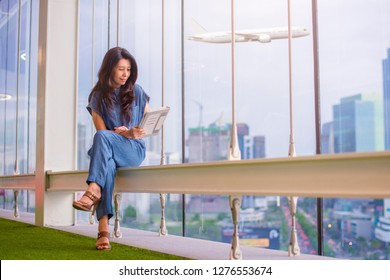 Asian female is watching news, doing online shopping so comfortable on digital tablet while sitting in front of windows in an office and Airplane in the sky with modern buildings on background.
