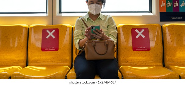 Asian female woman sitting in subway distance for one seat from other people a social distancing for protect coronavirus or covid-19 virus a new normal trend. Social distancing or new normal concepts