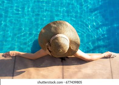 Las mujeres asiáticas viven relajantes y descansan cerca de la piscina de lujo, baños de sol, día de verano en el resort de playa en el hotel de vacaciones.  Concepto de verano.