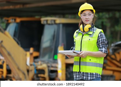 Asian female worker wear safety suits checking  of tracked excavator