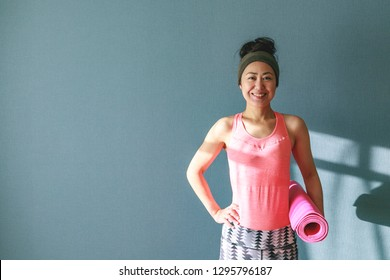 Asian female with the yoga mat