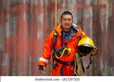 Asian firefighter smiling with uniform safety.Thai fireman prepare to train in firestation.Standing staff holding helmet and equipment.