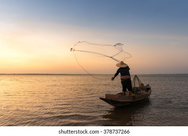 Asian fisherman on wooden boat casting a net for catching freshwater fish in nature river in the early morning
