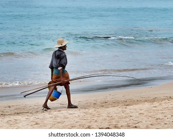 Asian fisherman walking on the beach. Mirissa, Sri Lanka, March 17, 2019.