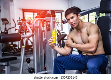 Asian fit man with energy drink relaxing and drinking in the gym. Sport and fittness concept.And Asian handsome muscles are tired, so drink Electrolyte drink.