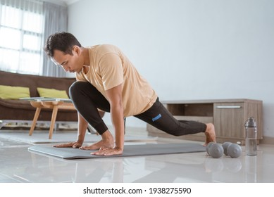 asian Fit Young Man Exercise Mat While Lifting One Leg and Looking to the Right.