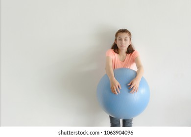 Asian fitness girl take a rest after practice Yoga with  blue stability ball exercises , So tired and sad. Copy space for text.