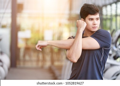 Asian fitness man warm up by stretching arms before exercises at the gym.  copy space.
