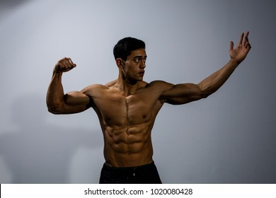 An Asian fitness model displaying his upper body physique. Medium shot.