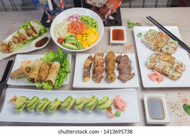 Asian food: assortments of sushi, maki, Japanese food. Served on a wooden table.