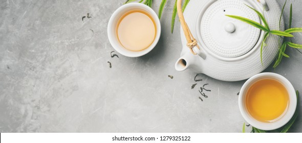 Asian food background set with green tea, cups and teapot with liefs and free space for text on grey concrete background. Flat lay. Long wide banner