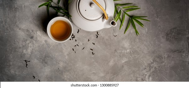 Asian food background set with  green tea, cups and teapot with liefs and free space for text on grey concrete background. Flat lay.