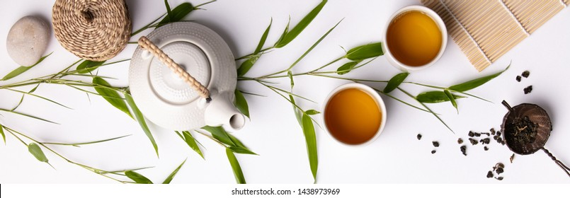 Asian food background set with green tea, cups and teapot with bamboo branches