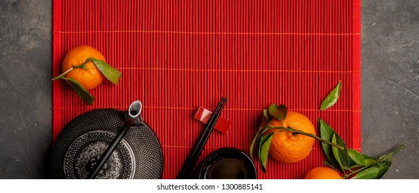 Asian food background set with tea, cups and pot, mandarin orange, chopsticks with leaves and free space for text on red bamboo mat. Flat lay of afternoon tea party.