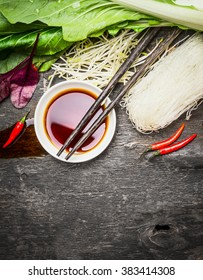 Asian food background with soy sauce, chopsticks, rice noodles and vegetables for tasty Chinese or Thai cooking, top view