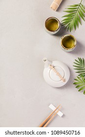 Asian food background - tea and chopsticks on a grey concrete background. Top view, flat lay