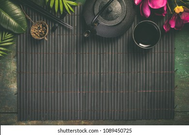 Asian food background - tea and chopsticks on dark rustic background. Top view, flat lay