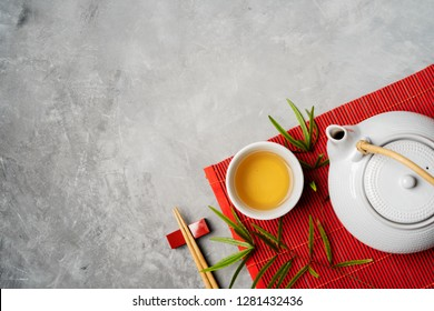 Asian food background with tea set and chopsticks on red bamboo mat on gray stone background. Top view with copy space.
