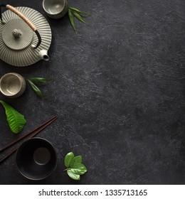 Asian food background - tea set, bowls and chopsticks on black background. Asian menu design, chinese japanese cuisine concept.