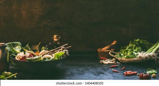 asiatischer Lebensmittelhintergrund. Wok Pfanne mit bunten Zutaten für koreanische vegetarische ein Topf. Heißes Topfzubereitung auf dunklem rustikalem Küchentisch. Gesunde veganische Küche