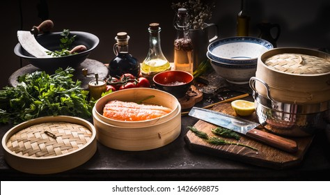 Asian food . Bamboo steamer with salmon fillet on dark rustic kitchen with various, seasoning, tools and ingredients . Cooking preparation.  Asian cuisine