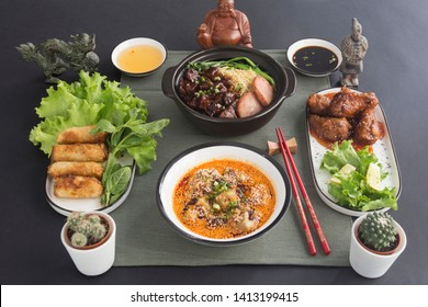 Asian food: beef with Shanghainese sauce, Korean fried chicken, ravioli with Shishuan sauce, nems with salad. Presented with Asian decoration, served on a green table mat.