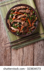 Asian Food: Bulgogi beef slices fried with sesame and carrot on a plate. vertical top view
