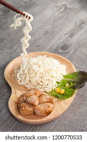 Asian food chopstick take nooddle with chicken fillet brown sauce on wood texture background