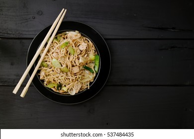 Asian food. Chow Mein. Noodles with vegetables and tofu on black wood surface. Top down. Flat lay.