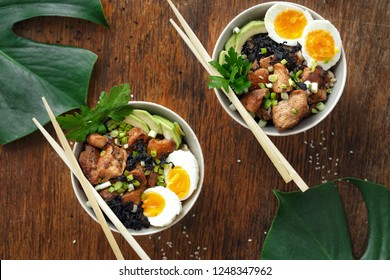 Asian food concept. Two poke bowl of fried rice, chicken fillet and eggs top view