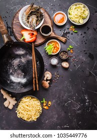 Asian food cooking concept, dark background. Empty wok pan, noodles, vegetables stir fry, shrimps, chopsticks. Space for text. Asian/Chinese food. Top view. Ingredients for making Asian/Chinese dinner