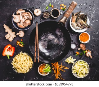 Asian food cooking concept. Empty wok pan, noodles, vegetables stir fry, shrimps, sauces, chopsticks. Asian/Chinese food. Top view. Ingredients for making Asian/Chinese dinner. Chinese noodles